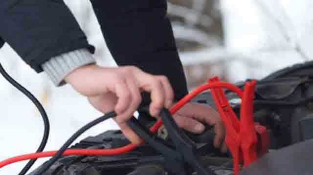 バッテリー上がりの車にブースターケーブルをつないでいるところ